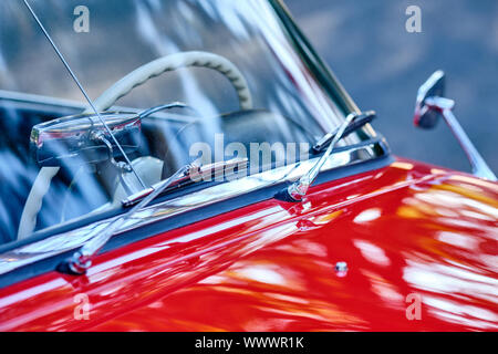 Detail with the windscreen, the wipers and the bonnet of a red colored vintage car - Stock Photo