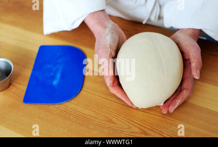 Chefs hand holding a clean finished dough. Closeup shot - Stock Photo