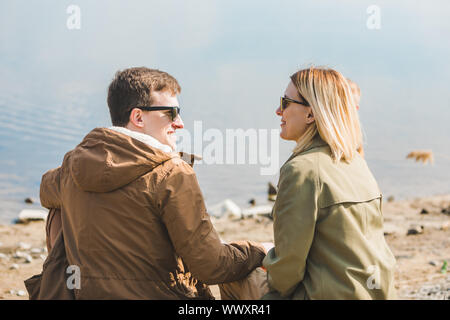 lovely smiling couple in autumn outfit sitting at beach in sunny day - Stock Photo