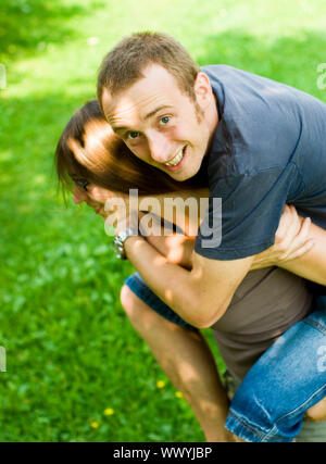happy young couple having fun outdoors doing piggyback rides with reversed roles - Stock Photo