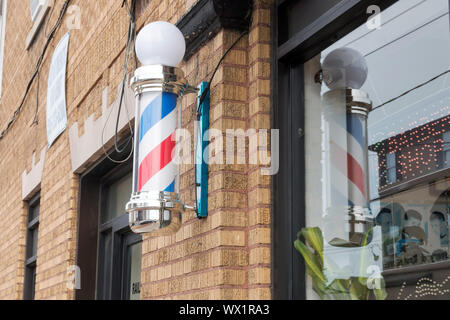 An old fashion Barber Shop Pole on the side of a brown brick building and a reflection of the pole in the window - Stock Photo