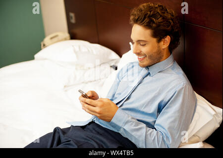Cool guy reading funny message on his cellphone. Enjoying during leisure time - Stock Photo