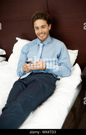 Adorable gentleman reading text sms on phone while lying on his bed in hotel room - Stock Photo