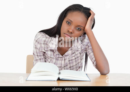 Student trying to read a book against a white background - Stock Photo