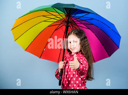 There is rainbow always after the rain. Rainy weather with proper garments. Rainy day fun. Happy walk under umbrella. Enjoy rain concept. Fall season. Kid girl happy hold colorful rainbow umbrella. - Stock Photo