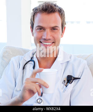Positive doctor having a break in the staff room - Stock Photo