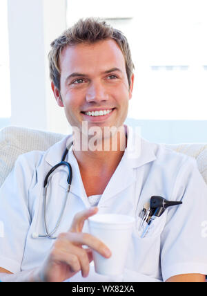 Charismatic doctor having a break in the staff room - Stock Photo
