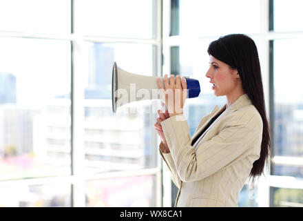 Attractive young businesswoman shouting through megaphone - Stock Photo