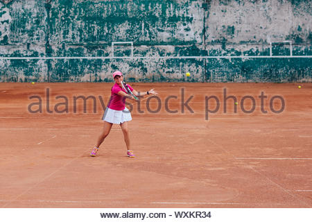 Tennis player. Happy sportive woman playing tennis, receiving a ball, dressed in pink t-shirt, cap and white skirt. Side view, on the court. - Stock Photo