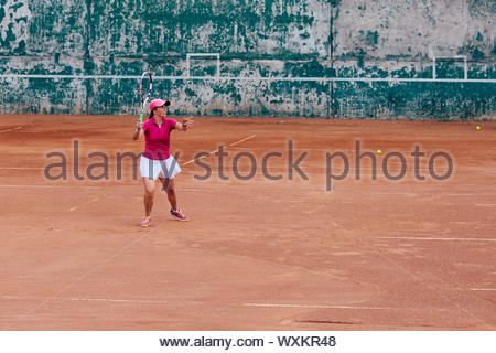 Tennis player. Athlete woman playing tennis, receiving a serve, dressed in pink t-shirt, cap and white skirt. Side view, on the court. - Stock Photo