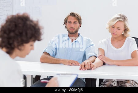 Psychologist taking notes while couple speaks - Stock Photo