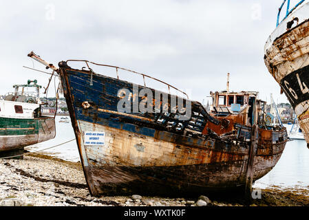 Camaret-sur-Mer, France - August 4, 2018: Old abandoned shipwrecks in the old boat cemetery, Cimetiere de bateaux, at Le Sillon a cloudy day of summer - Stock Photo