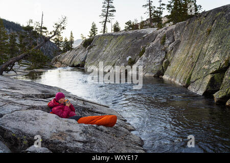 Backpacking off trail in Desolation Wilderness at Ropi Lake morning coffee in sleeping bag next to stream with pyramid peak in background. - Stock Photo