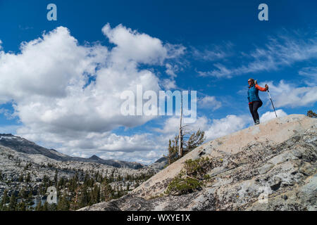 Female hiker Backpacking off trail in Desolation Wilderness looking back at Desolation Lake - Stock Photo