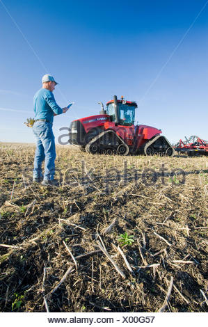 farmer using a tablet in front of a tractor and air seeder, planting winter wheat in a zero till field containing canola stubble, near Lorette, Manitoba, Canada - Stock Photo