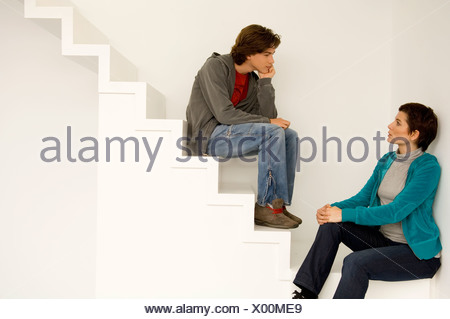 Mid adult woman and her son sitting on a staircase - Stock Photo