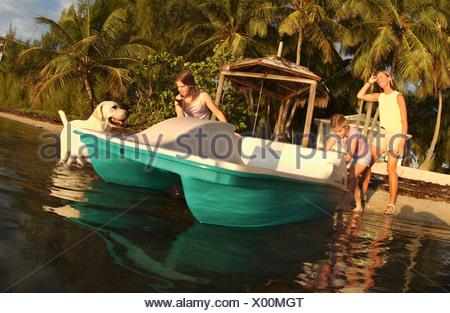 Sisters ready a new paddleboat, Florida. - Stock Photo
