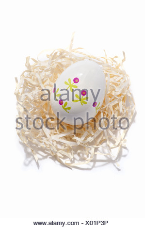 A decorated Easter egg on a paper straw nest - Stock Photo