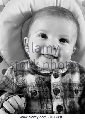 Directly Above Shot Of Happy Baby Boy Lying On Bed - Stock Photo