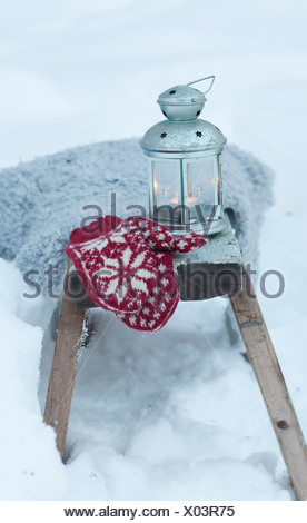 Mittens and lantern in snowy field - Stock Photo