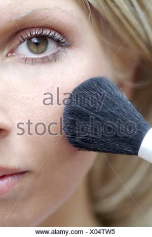 Junge Frau pudert sich das Gesicht mit einem Pinsel ab - Stock Photo
