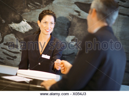 Woman behind counter smiling, handing object to man - Stock Photo