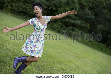 A young woman in a summer dress with her arms outstretched celebrating freedom - Stock Photo