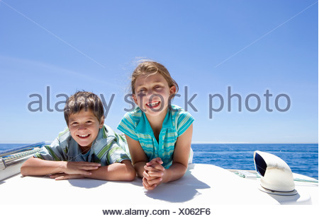 Boy and girl  lying on front on deck of sailing boat out at sea, side by side, smiling, front view, portrait - Stock Photo