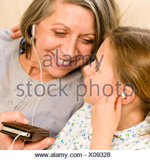Grandmother and young girl listen music together - Stock Photo