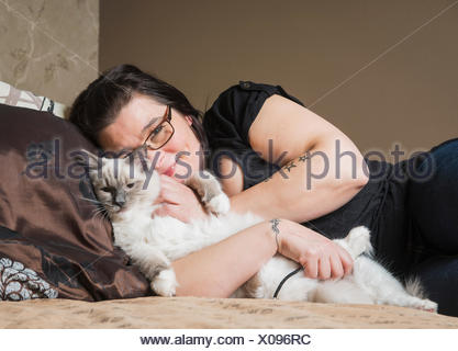 Portrait of Ragdoll cat with owner, relaxing on bed - Stock Photo