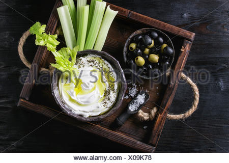 Fresh celery with yogurt and olive oil dip in ceramic bowl, served with sea salt and black, green olives on wood tray over black wooden burnt backgrou - Stock Photo