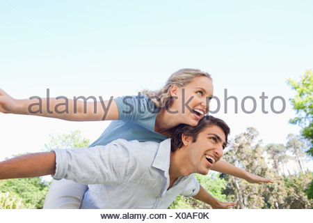 Man carrying his his friend on his back while she spreads her arms - Stock Photo