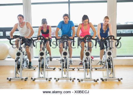 Determined people working out at spinning class in gym - Stock Photo