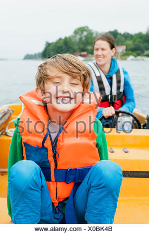 Sweden, Uppland, Runmaro, Barrskar, Portrait of boy (6-7) on motorboat, mother in background - Stock Photo