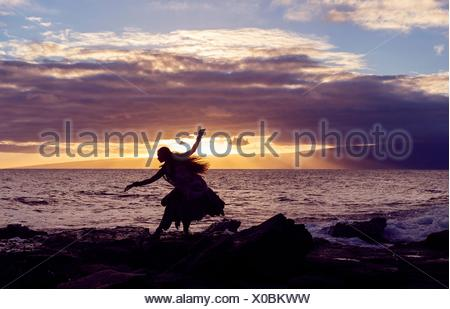 Silhouetted woman hula dancing on coastal rocks wearing traditional costume at sunset, Maui, Hawaii, USA - Stock Photo