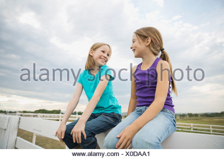 Smiling sisters sitting on railing looking at each other - Stock Photo