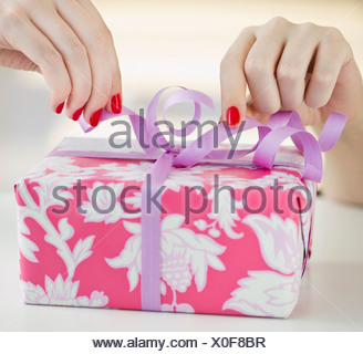 Tying a bow on a present - Stock Photo