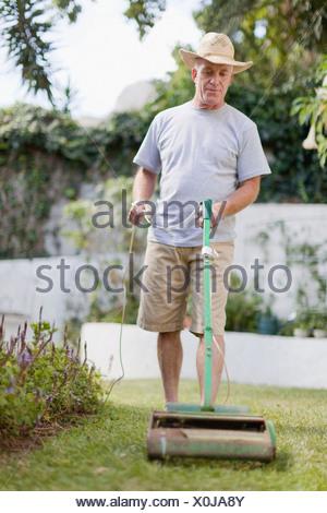 Older man mowing lawn in backyard - Stock Photo