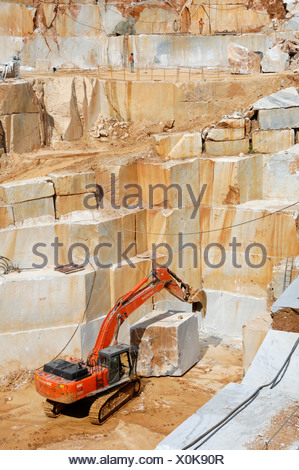 Mechanical shovel excavator is moving a heavy marble stone cuboid in a marble quarry in Colonatta near Carrara, Tuscany, Italy - Stock Photo