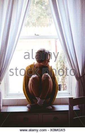 Young woman sitting on a table - Stock Photo