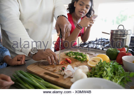 African American father and daughter cooking in kitchen - Stock Photo