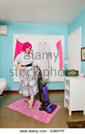 Portrait of a happy young woman vacuuming carpet - Stock Photo