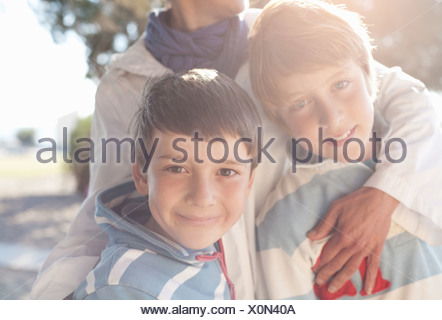 Two boys being hugged by woman - Stock Photo