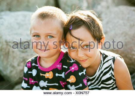 Portrait of brother and sister smiling while sitting on rocks in park - Stock Photo