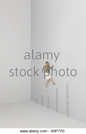 Woman walking up steps made of stacked water bottles - Stock Photo