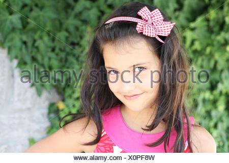 Sweet smiling little girl (6-7) with long dark hair on green ivy background - Stock Photo