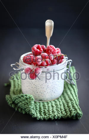 Raspberry,red currant and chia seeds pudding in jar for breakfast - Stock Photo