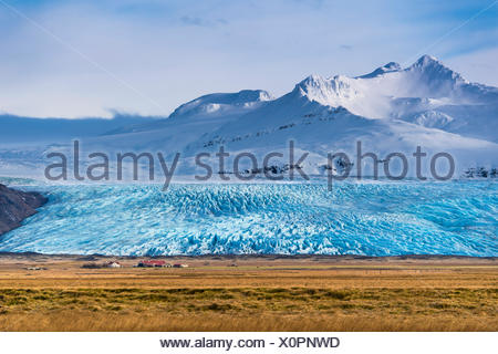 Icelandic farmstead with glacier tongue and snow-covered mountains, Höfn, Iceland - Stock Photo