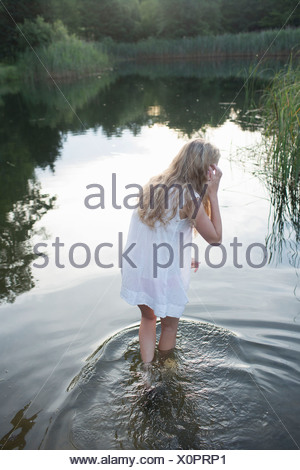Teenage girl enjoying river in the evening - Stock Photo