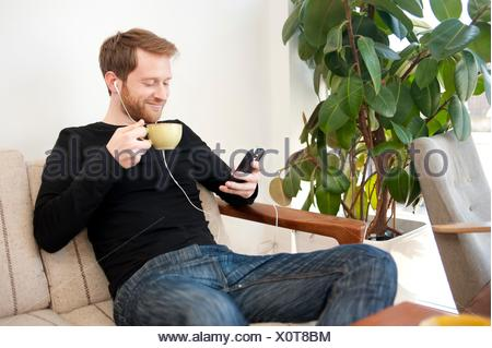 Male customer selecting music on smartphone in cafe - Stock Photo